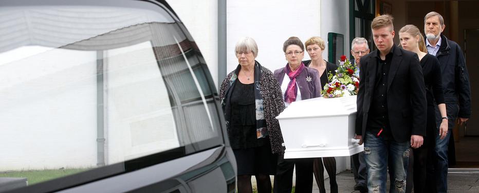 Pårørende bærer kisten ud til rustvognen.