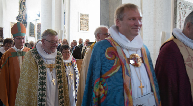 Procession af biskopper i farvestrålende bispekåber.
