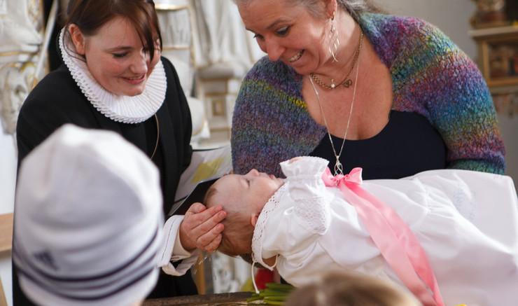 Præsten døber barnet.