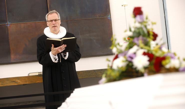 Præsten holder en tale foran afdødes kiste.