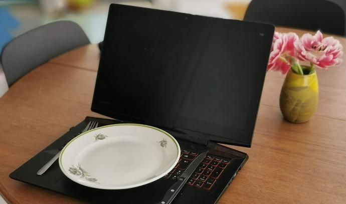En tallerken med bestik, som står på en åben bærbar computer,