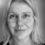 Billede ansigtet og øvre torso af en lyshåret kvinde med briller
