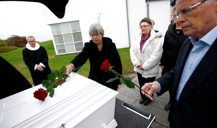 Pårørende i sorg tager afsked ved kisten, inden rustvognen kører kisten væk.