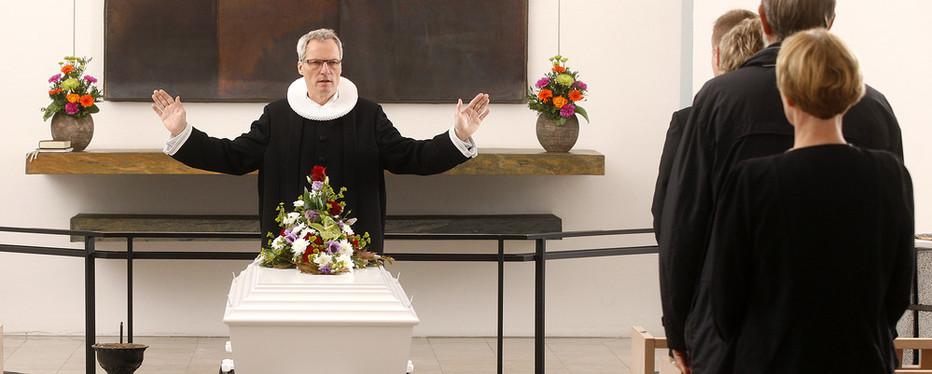 Præsten lyser velsignelsen over afdøde.