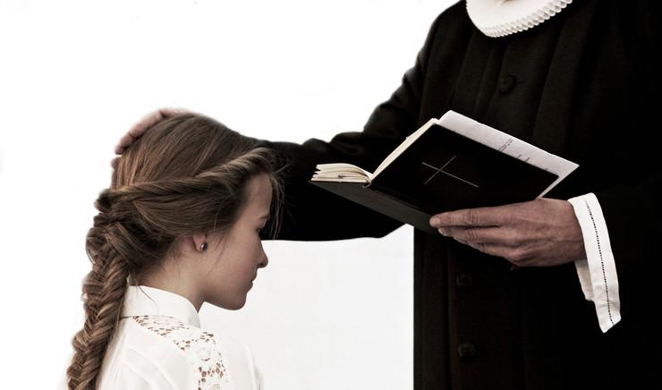 Præsten velsigner konfirmanden.